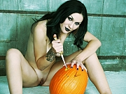 Naked white skinned and black haired Lady carving a pumpkin